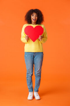 Full-length vertical shot lovely charismatic and dreamy african-american woman in sweater, jeans, holding big red heart as searching soulmate, date for valentines day, orange background