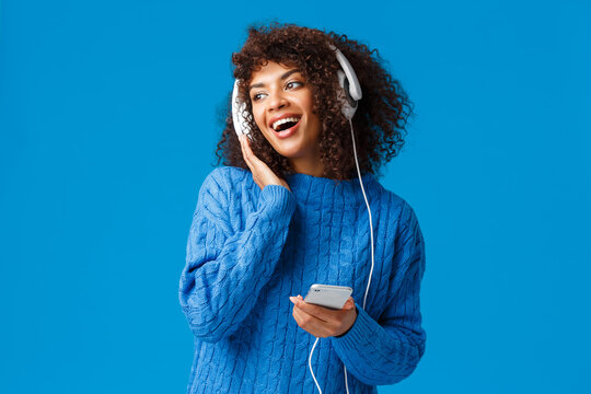 Charismatic modern young attractive african-american girl with afro haircut, listening music in headphones looking out window snowy weather, holding smartphone, smiling and singing