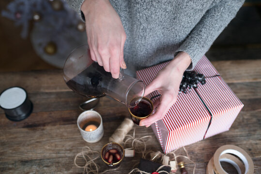 Woman pouring mulled wine while packing present, Sweden