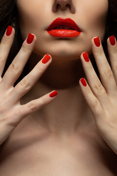 Beautiful young model with red lips and red manicure.