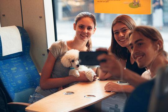 Friends taking selfie in train, Sweden