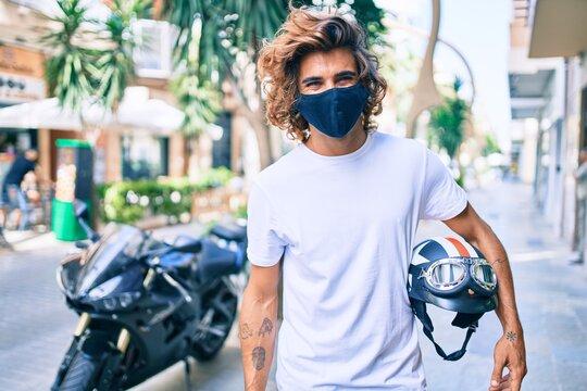 Young hispanic man wearing coronavirus protection mask holding moto helmet over motorcycle at the city