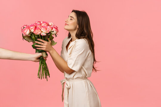 Romance, valentines day and happiness concept. Gorgeous young woman receiving delivery, smelling pretty roses as hand extending bouquet to girl, smiling delighted, got surprise gift, pink background