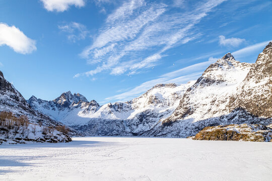 Winter landscape with frozen fjord and snow covered mountains in a sunny day. Lofoten islands, Norway.