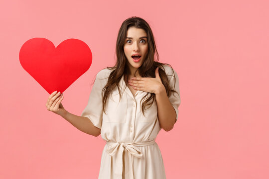 What an unexpected surprise. Love, relationship and valentines day concept. Touched and amazed tender lovely girlfriend receive heart card, looking amazed and astonished, pink background