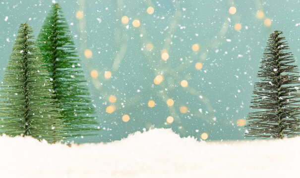 Miniature toy Christmas trees on a wooden table with snow. Imitation realistic scene. Banner