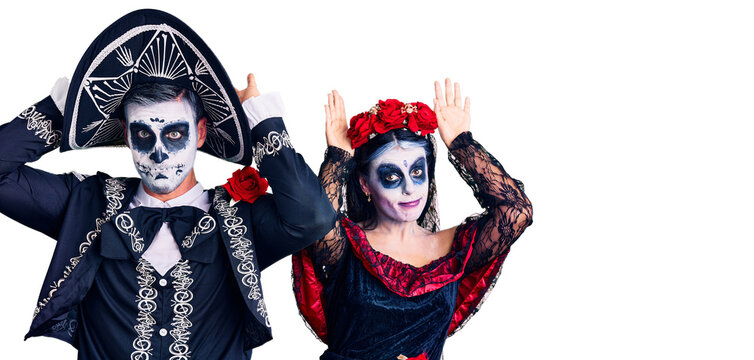 Young couple wearing mexican day of the dead costume over background doing bunny ears gesture with hands palms looking cynical and skeptical. easter rabbit concept.