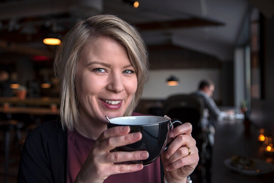 Smiling woman holding tea cup, Sweden