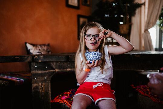 Girl holding bowl and eating, Sweden
