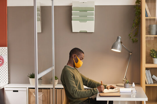 Side view portrait of young African-American man wearing mask and writing in planner while working at desk in office cubicle, copy space