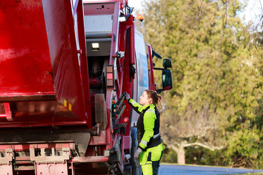 Woman operating garbage truck, Sweden