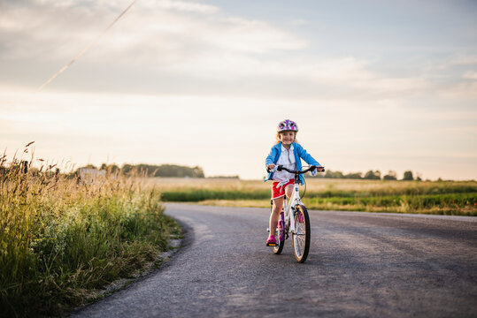 Girl cycling on country road, Sweden