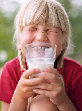Smiling girl holding glass of milk, Sweden