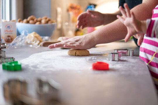 Mutter und Kind formen den Teig zum Kekse backen
