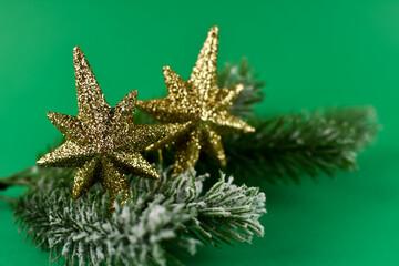 Fototapeta Złote, bożonarodzeniowe gwiazdki na gałązce choinki. obraz