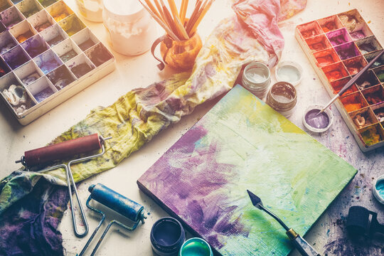 Artistic equipment: canvas and palette knife, paint brushes, multicolored paints in artist studio. Top view.