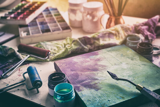 Artistic equipment: canvas and palette knife, paint brushes, multicolored paints in artist studio.