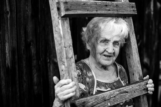 An old woman portrait in the village. Black and white photo.