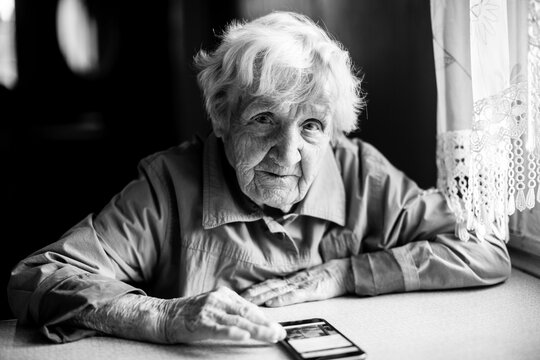 An old woman sits with a smartphone. Black and white photo.