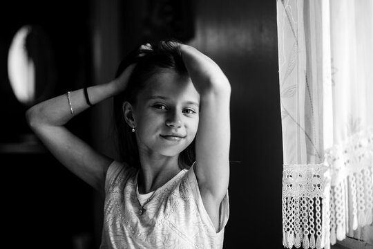 Ten-years-old posing for the camera sitting at the table. Black and white photography.
