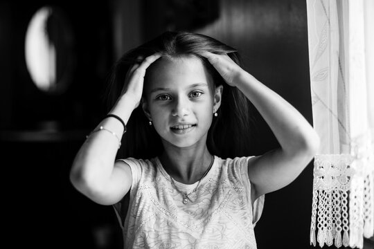 Ten-years-old posing for the camera sitting at the home. Black and white photo.