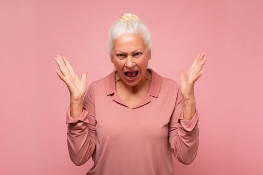 Frustrated and angry senior hispanic woman screaming.