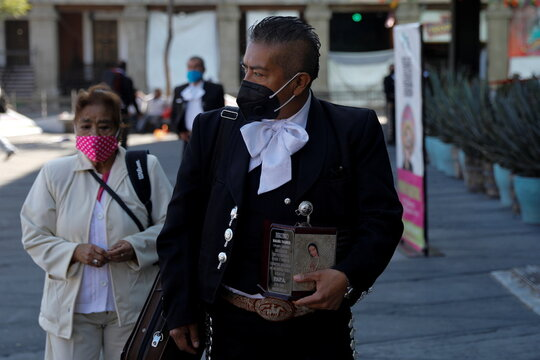 Mariachi Sergio Magana carries the ashes of his late mariachi father, who died of COVID-19, as he pays homage to Saint Cecilia, the patron saint of musicians, during the annual celebration as the coronavirus disease (COVID-19) outbreak continues, in Mexico