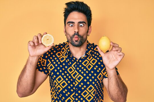 Handsome hispanic man with beard holding lemon making fish face with mouth and squinting eyes, crazy and comical.