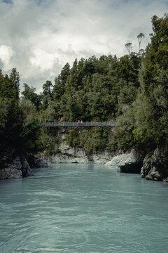 Two people crossing suspension bridge in Hokitika Gorge Scenic Reserve. West Coast, New Zealand, South Island