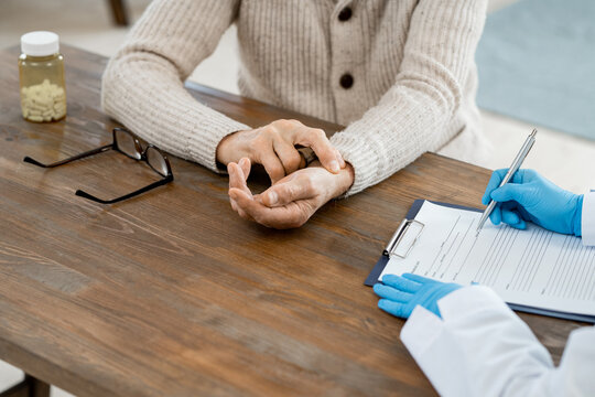 Gloved hands of female doctor with pen over medical paper making prescriptions