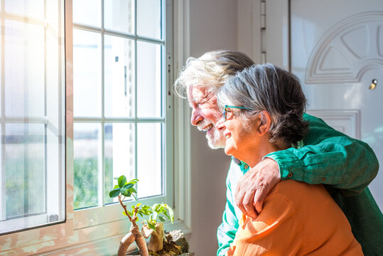 couple of two cute old and mature people or seniors having fun together at home looking outside of their house smiling and laughing