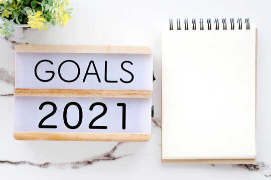 2021 goals on wood box and blank notebook paper on white marble background, 2021 business new year aim to success