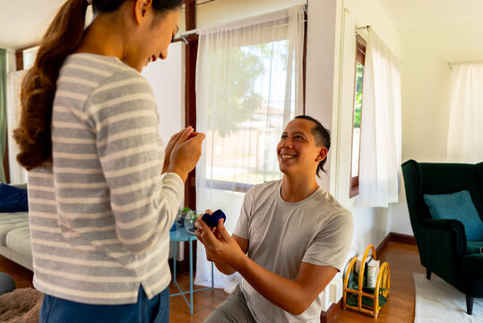 Young man proposing his girlfriend with engagement ring at home. Asian woman getting surprised by her boyfriend with marriage proposal