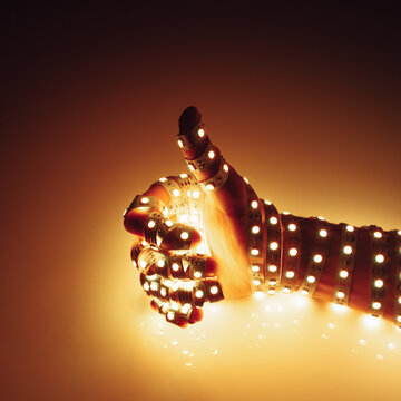 thumbs up hand covered with warm yellow led lights, illuminated background