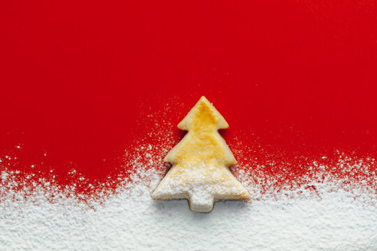Christmas tree cookie and floury snow, red paper background