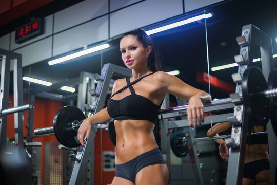 Beautiful sporty sexy woman is posing near a barbell after training in gym