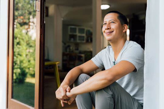 Portrait of 30-40 year happy smiling and thoughtful man sitting on the front door at home in summer. Mixed race of Asian and Caucasian guy looking away - with copy space