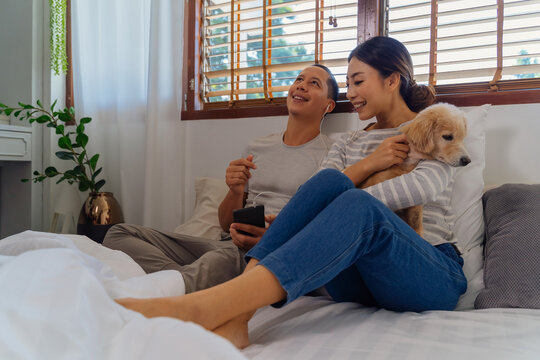 Portrait of happy young adult Asian couple on bed along with dog pet in bedroom interior scene. Man and woman are listening to music together. Marriage and happy relationship life concept