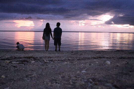 Asian couple watching the sunset at the beach.