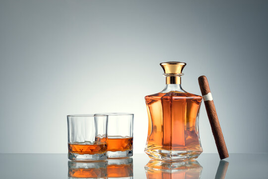 close up view of cigar, bottle of whiskey  and a glasses aside on grey back.