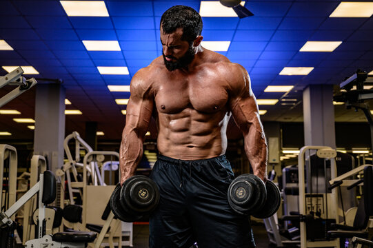 strong young caucasian bearded athlete with dumbbells workout heavy in sport fitness gym