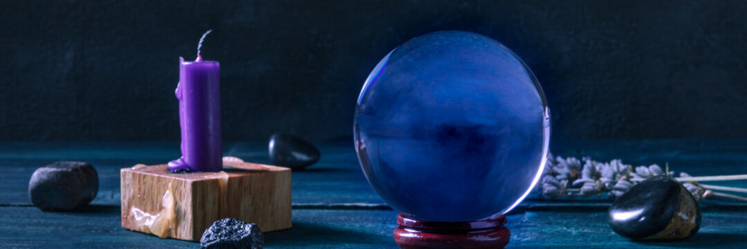 Fortune telling panorama. A magic ball with a candle, crystals and herbs, a side view on a dark background