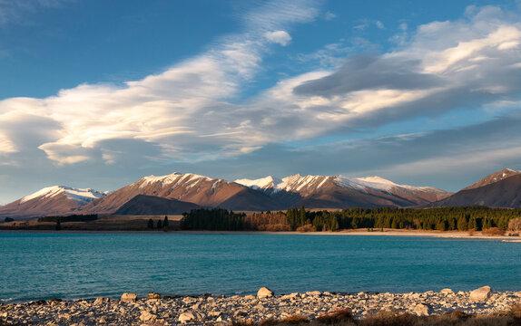 Sunsen on rocky shore of lake Tekapo, New Zealand