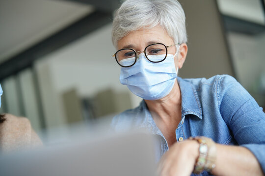 55-year-old senior woman with white hair working with face mask