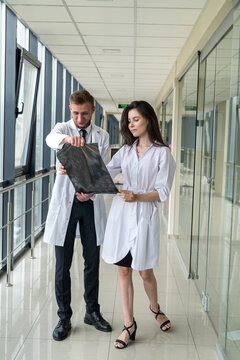 Two healthcare professionals looking at x-ray image,  mri brain  of patient for diagnosis
