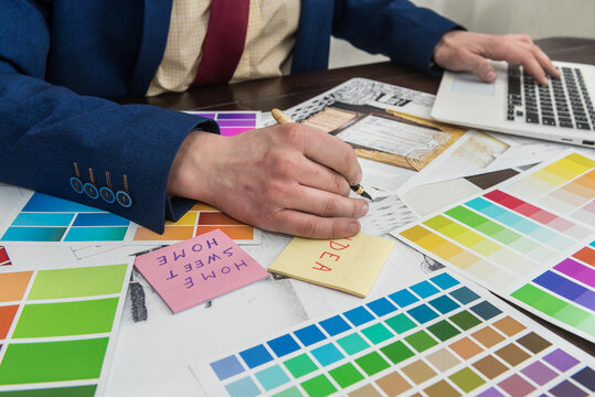 Architects hands drawing of modern apartaments with colour sample and laptop on creative desk, office. Man choosing colors for room decoration.