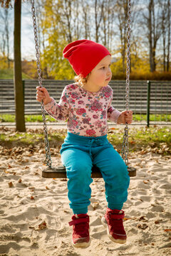 Cute baby girl on a swing in a playground