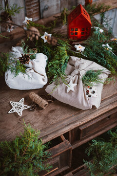 Christmas gifts wrapped in Japanese-style furoshiki fabric in coniferous branches of fir and spruce.
