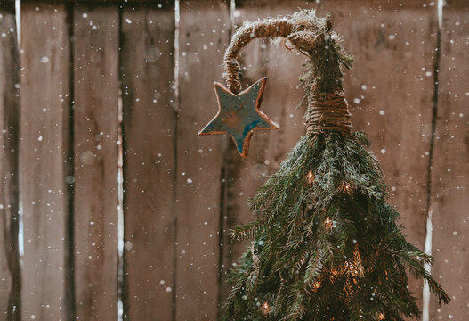 Handmade Christmas tree with a star on a curved top on a wooden background.
