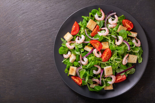 plate of fresh salad with shrimps, greens and tomato, top view